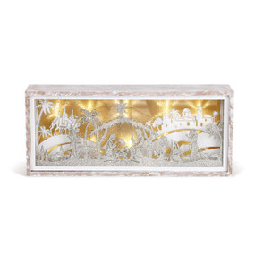 Side view of white/gold lantern with palm trees and nativity scene carved in