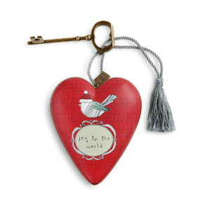 Small red heart pendant with white banner and 'joy to the world 'in black below an image of a bird - gold key and silver tassle attatched