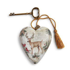 Small tan colored heart pendant with green holly branches and brown deer in the center - gold key and tassle attatched