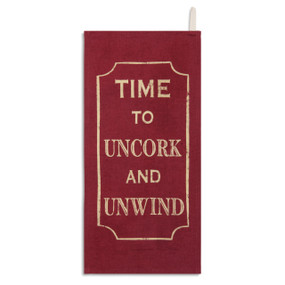red kitchen towel reading Time to Uncork and Unwind