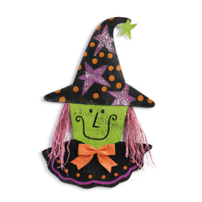 metal wall hanging painted like a witch with straw hair