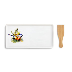 A white appetizer tray with a chickadee bird and ferns painted on the left side. Placed beside a wooden spatula.