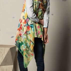 A pink, orange, red, and green floral print scarf vest on a white and wooden mannequin.