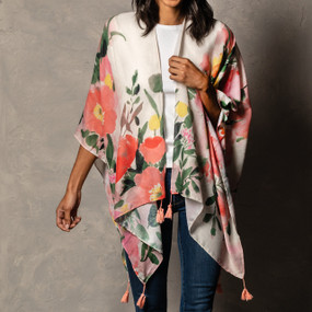 A white kimono with a pink and green floral print and pink tassels on a white and wooden mannequin.