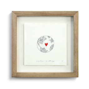 A simple scribble drawing of the earth with a red thread heart in a wooden frame.