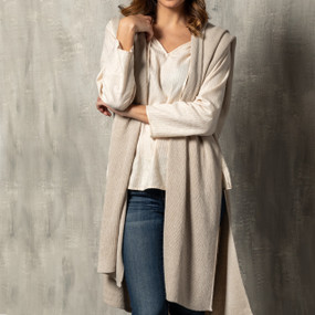 """A large taupe """"Recycled Knit Duster"""" on a white and wooden mannequin."""