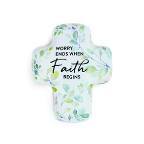 """A light blue art cross with green and yellow flowers that reads """"worry ends when faith begins""""."""