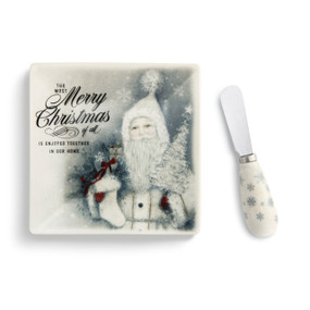 A white square plate with a Christmas message and a Santa Claus lying beside a matching spreading knife.