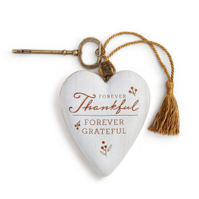 """A white art heart with """"forever thankful forever grateful"""" in red font with a bronze key and a gold tassel."""