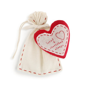 A white fabric gift bag with a red and white fabric ornament.