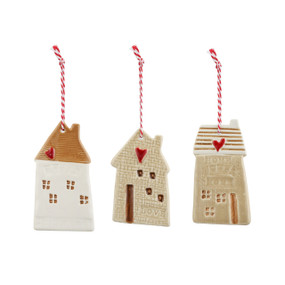 A set of three ceramic gingerbread houses hanging from a red and white string.