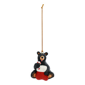 Hanging black bear ornament with the bear sitting and holding a stocking and candy cane