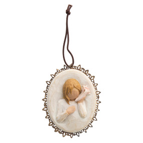 Round pendant with young girl holding pink shoe to her ear