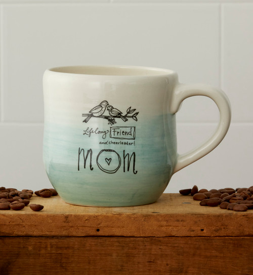 Mug sits on brown shelf with coffee beans on either side. White cinder block background