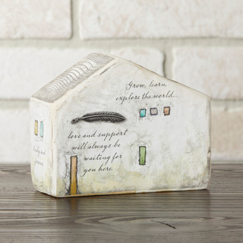 White small house figurine with black feather and 'grow, learn, explore the world...love and support will always be waiting for you here' in black - white brick wall background