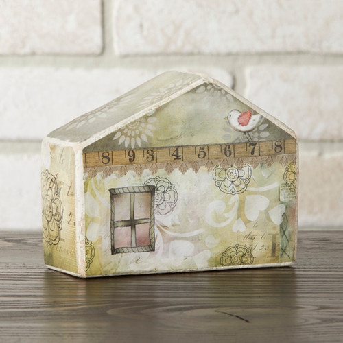 Small light grey/yellow house figurine on wooden surface