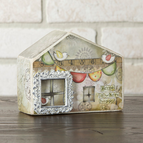 Small light tan house figurine with windows and ruler and birds printed on - sitting on dark wooden counter