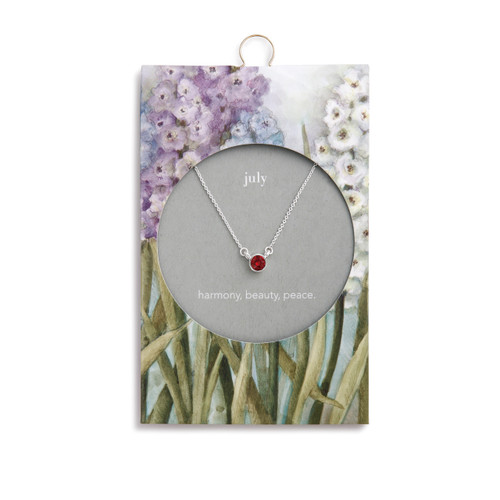 Silver chain necklace holds a red stone. Necklace is on a message card with white lettering and purple, blue, and white bunches of flowers.