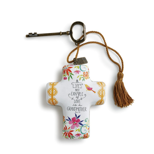 White cross with gold decals on left and right arm and colorful doodles on top and bottom. Black lettering. Bronze key and tassel are attached to top of cross