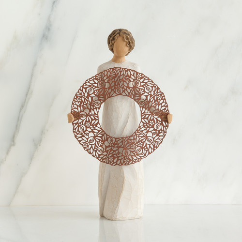 Faceless woman figurine standing in white dress holding brown round wreath figurine