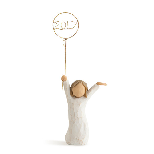 Small girl figurine in white dress holding up balloon that says 2017 on it