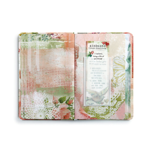 Gift book is open. Pink, green, and white pages, and pocket sleeve holding magnet book mark is on the right page