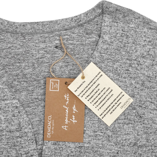 Close view of grey shirt with two white and brown demdaco tags on it