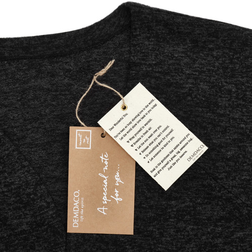 Close view of black shirt with two demdaco tags in white and brown on it