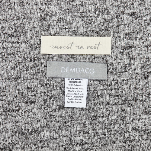Close view of light grey fabric with 'invest in rest' demdaco' tag