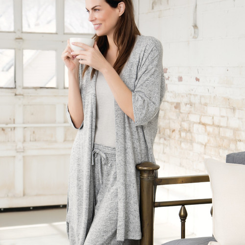 Side profile of dark haired woman in grey sweats and shawl holding coffee cup