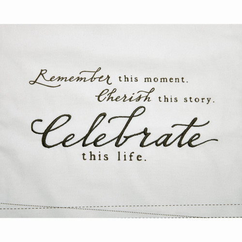 Close view of white fabric and 'remember this moment cherish this story celebrate this life' in black