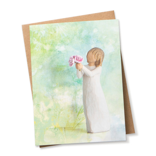 Notecard with blue and green background and figurine holding pink flowers sits on top of a brown envelope