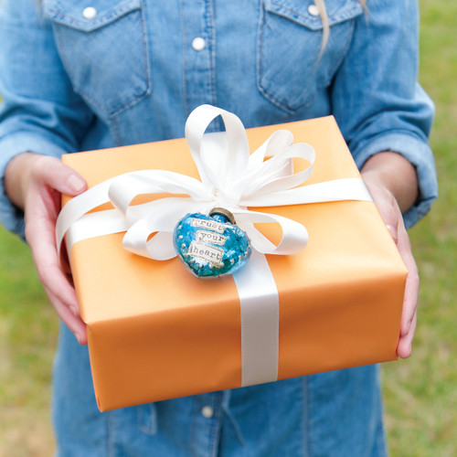 Close view of hands holding orange present box wrapped in white bow and blue heart pendant