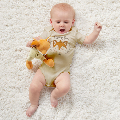 baby laying on white rug wearing Clever Fox onesie holding stuffed animal fox