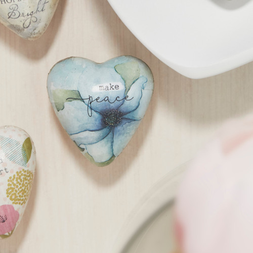heart trinket with blue flower reading Make Peace