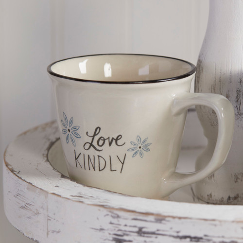 mug on wooden shelf reading Love Kindly with two blue flower illustrations