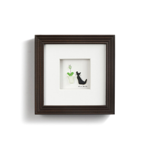 pebbles and seaglass depicting cat sitting next to flowerpot with white background in dark frame