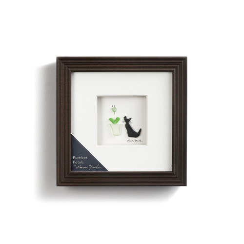 Close view of dark brown wall art with black cat figurine next to flower pot centered