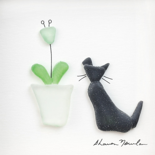 Close view of black pebble cat next to white flower pot with green stems