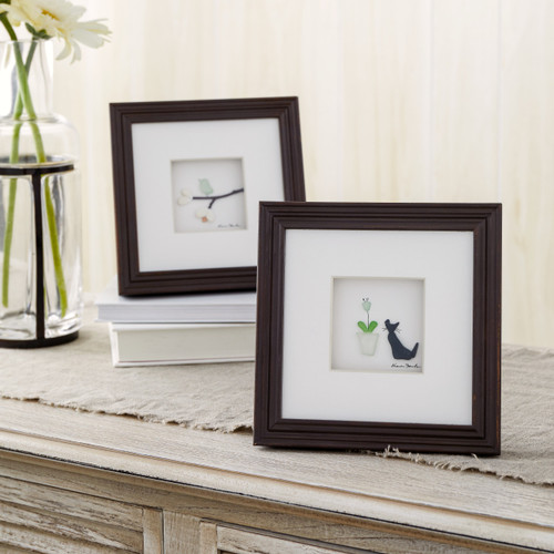 two dark wooden frames depicting a cat sitting next to a flowerpot and a bird on a tree branch sitting on a dresser