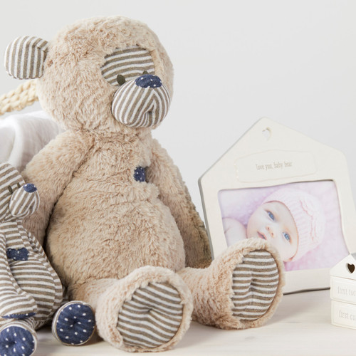 stuffed animal bear in sitting position next to white ceramic house shaped frame