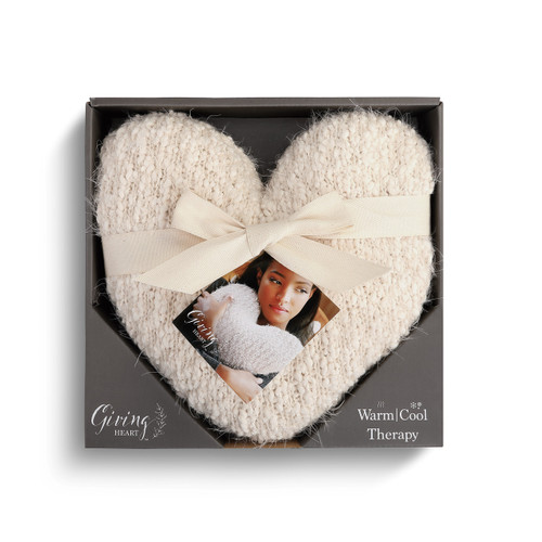 white knit heart shaped pillow with white ribbon wrapped around it inside gray cardboard box