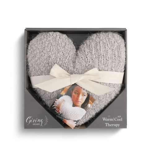 gray knit heart shaped pillow with white ribbon wrapped around it inside gray cardboard box