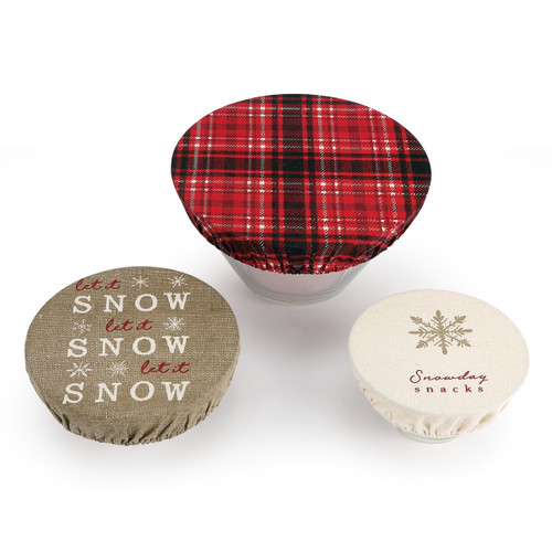 three elastic bowl covers on bowls, one red and black plaid, one with snowflake ilustration reading Snowday Snacks, and one tan reading Let it Snow Let it Snow Let it Snow