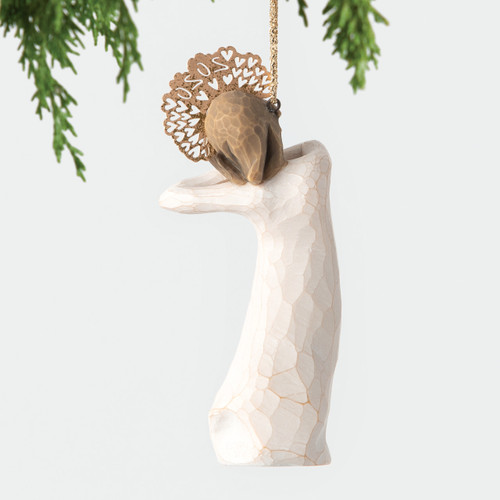 Back view, figure in cream dress, hands clasped under chin, with 2020 cut into gold metal headpiece. Hook, loop affixed to head