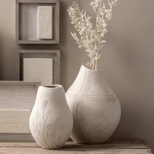 A set of two white asymmetrical vases. One with flowers engraved, one with a cross engraved.