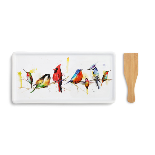 A white appetizer tray with seven little birds painted across. Placed beside a wooden spatula.