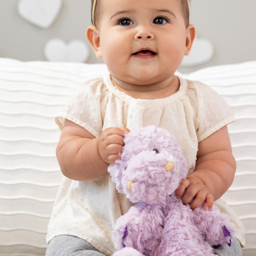A close up image of a baby girl, sitting in front of two large pillows in a nursery scene, holding a soft, plush, purple and yellow T-Rex Rattle Blankie.