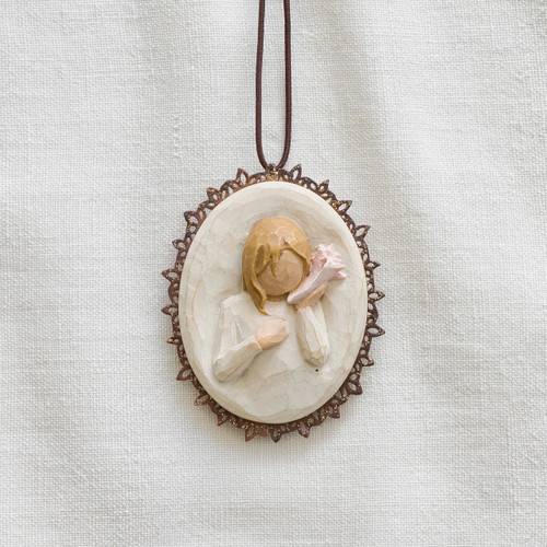 Close view of cream round pendant with carved in image of blonde girl figurine with seashell up to her ear