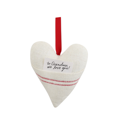 """A red and white plush heart pocket ornament with a note that reads """"To Grandma, we love you!""""."""